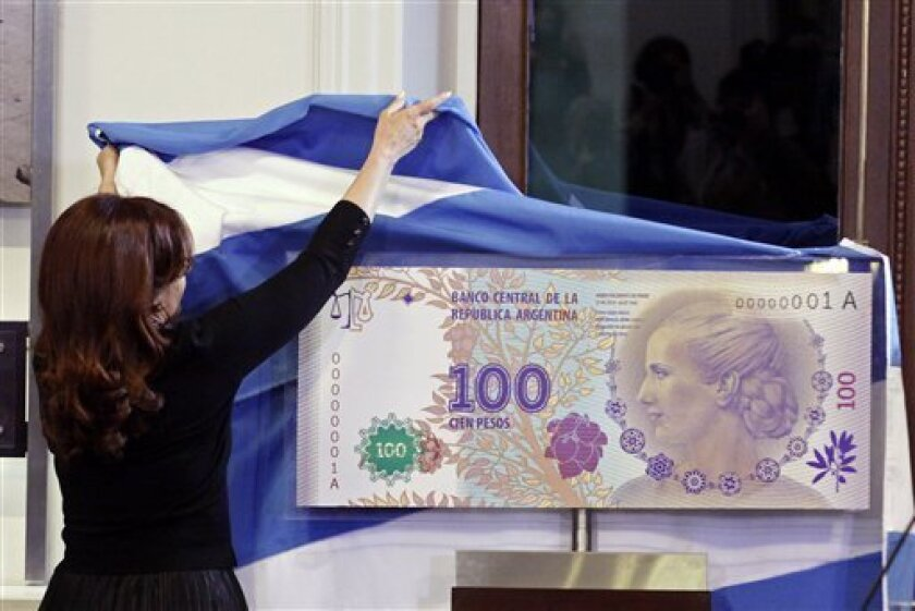 """FILE - In this July 25, 2012 photo, Argentina's President Cristina Fernandez unveils an archetype of the new 100 Argentine pesos bill bearing the profile of former late first lady Maria Eva Duarte de Peron, better known as """"Evita,"""" at the government palace in Buenos Aires, Argentina. Judgment day i"""