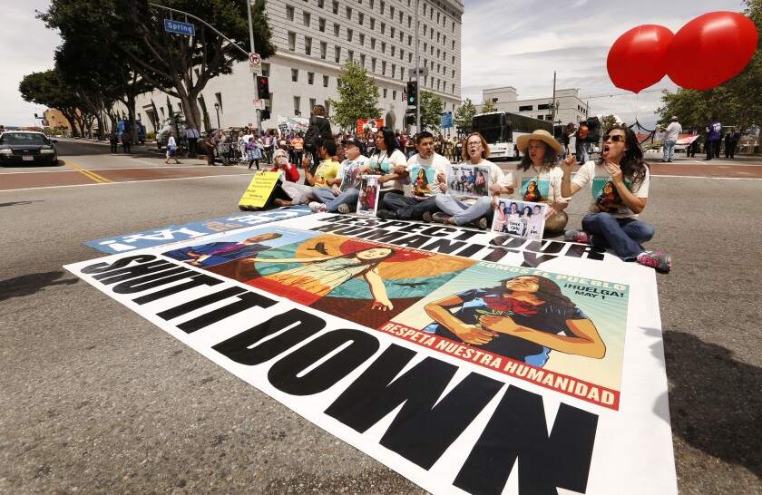 "Protesters take a seat on Spring Street at Temple in downtown Los Angeles as part of the ""Caravan Ag"