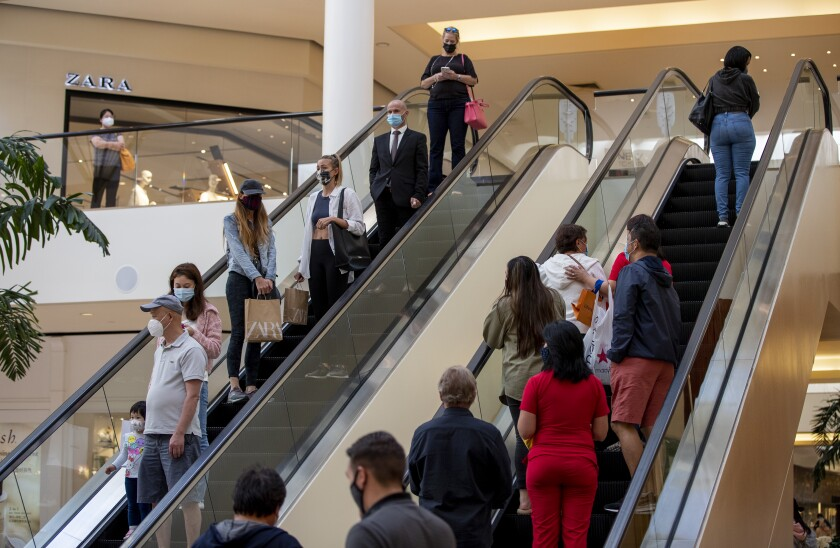 Shoppers on escalators at South Coast Plaza wear masks.