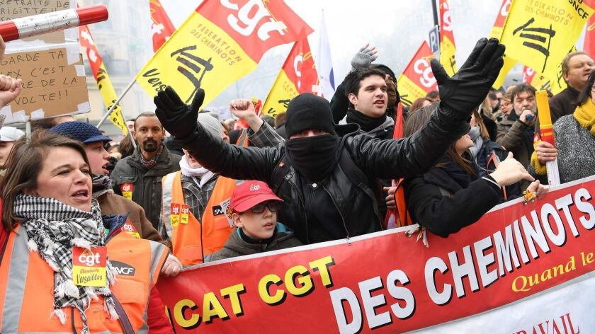 People take part in a demonstration on March 22, 2018, in Paris as part of a nationwide day of protest against the French president's multi-front reform drive.