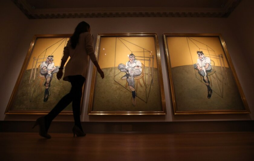 A staff member of Christie's in London walks past Francis Bacon's triptych of artist Lucian Freud last year. It later fetched $142 million, the highest auction price to date for an artwork.