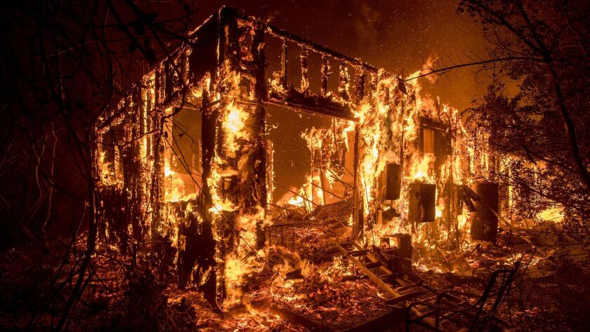 Flames consume a home as a wildfire burns in Ojai, Calif., on Dec. 7.