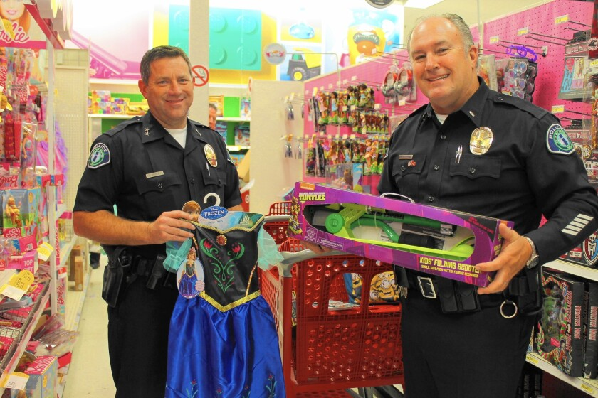 Irvine police Cmdr. Matt Mahony and Lt. Frank Andersen shop at a Target store to find gifts for children attending the Shop With a Cop holiday party.
