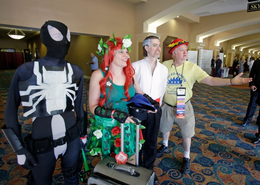 A Libertarian delegate, far right, poses with comic charters attending a convention next door to the National Libertarian Party Convention in Orlando on Friday.