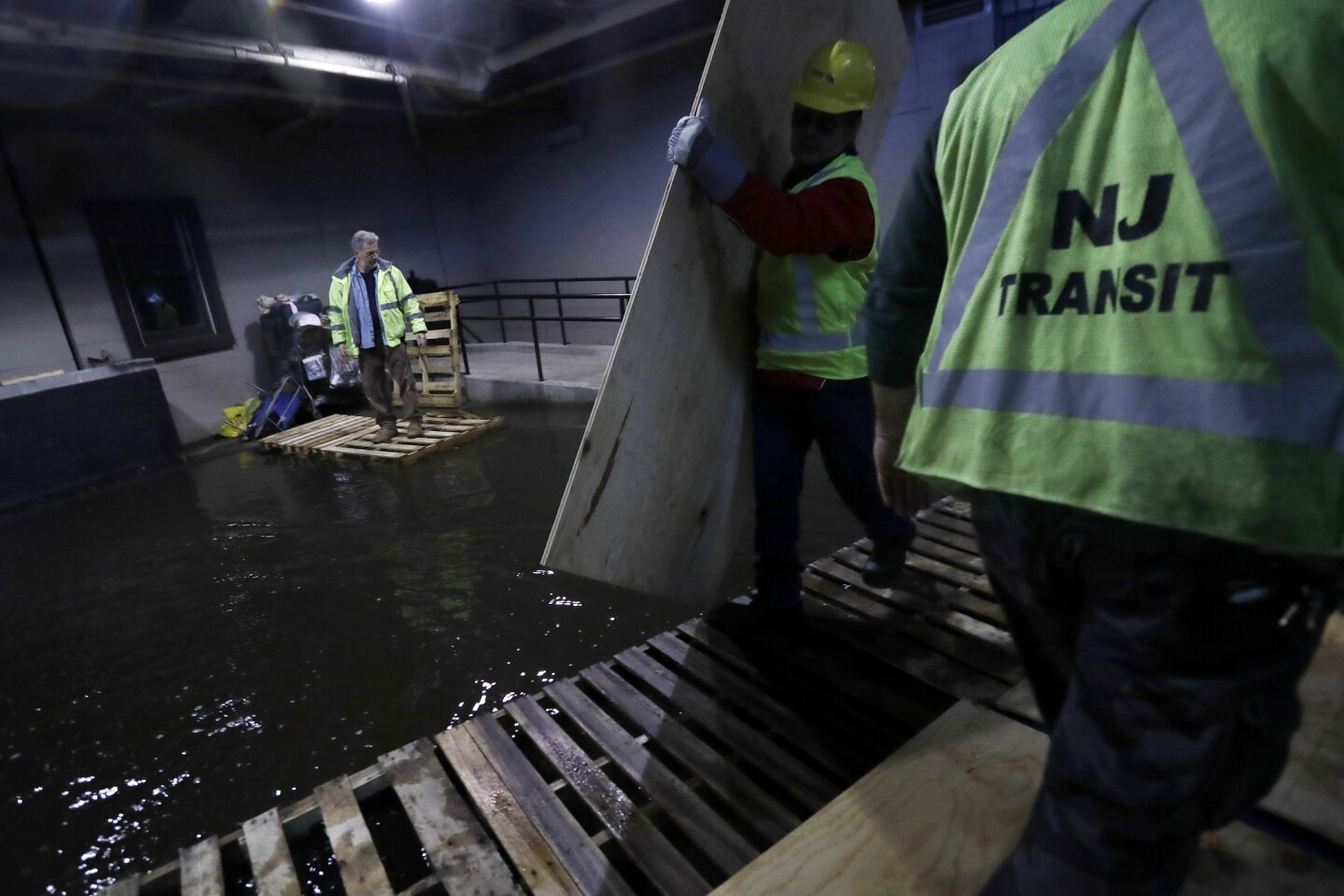 New Jersey Transit workers lay down pallets and boards for commuters to walk on a flooded hallway adjacent to the site of a train crash at the Hoboken Terminal on Sept. 30, 2016.
