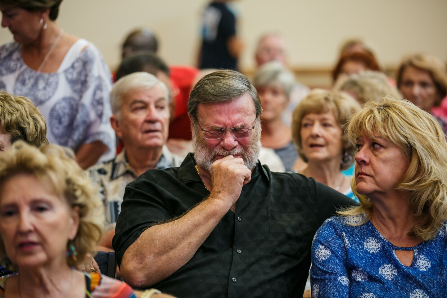 Wayne Christopher, center, weeps as his wife, Helen Christopher, looks on during the first Sunday service since Tropical Storm Harvey caused widespread flooding and damaged the First United Methodist Church.