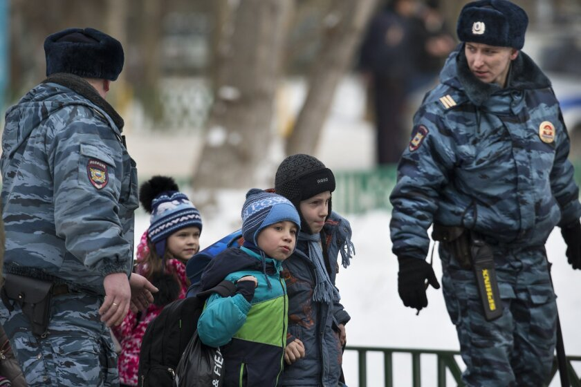 Police officers evacuate children from a Moscow school on Monday, Feb. 3, 2014. An armed teenager burst into his Moscow school on Monday and killed a teacher and policeman before being taken into custody, investigators said. None of the children who were in School No. 263 were hurt, said Karina Sabitova, a police spokeswoman at the scene. The student also wounded a second police officer who had responded to an alarm from the school, she said. (AP Photo/Alexander Zemlianichenko)