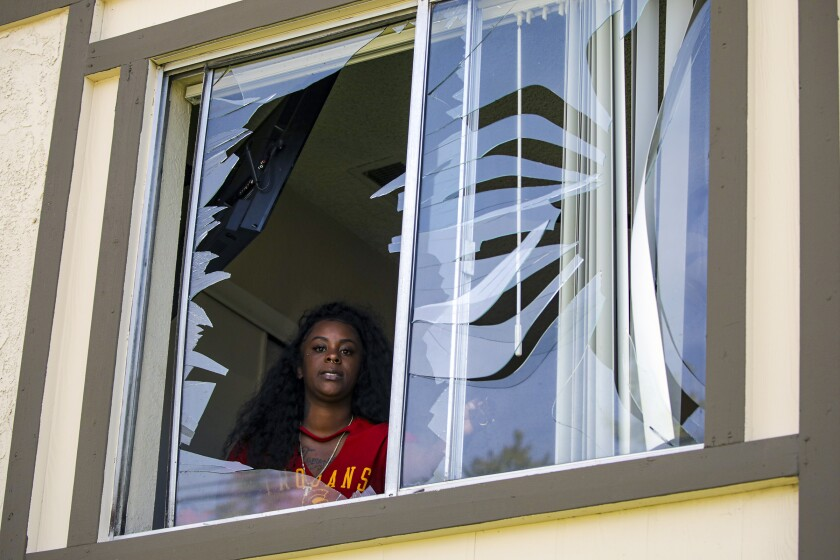 A woman looks out a broken window.