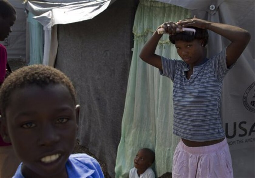 A woman combs her hair outside her tent at a makeshift camp for earthquake survivors in Port-au-Prince, Tuesday, March 16, 2010. Women, girls and children as young as 2 years old, already traumatized by the loss of homes and loved ones in Haiti's earthquake, now are falling victim to rapists in spr