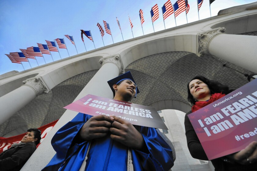Jose Montes, 19, sporting his graduation cap and gown from Compton High School, and Paula Sarrad listen Tuesday at L.A. City Hall as speakers talk about expanded federal immigration programs.