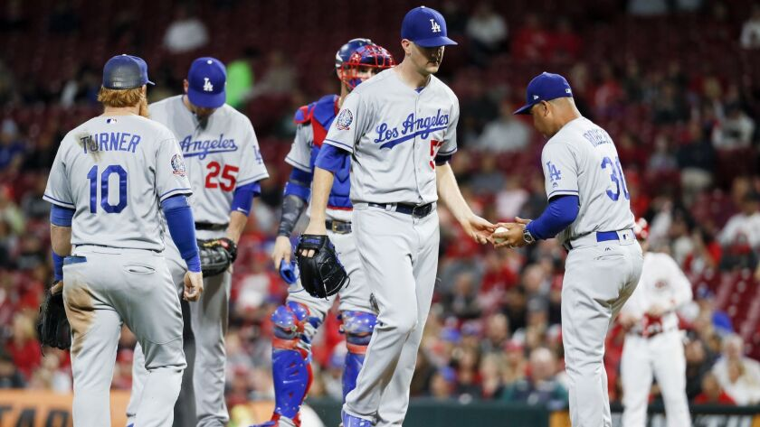 Dodgers starting pitcher Alex Wood, center, is taken out of the game in the fourth inning against the Cincinnati Reds.