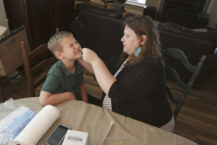 Mendy McNulty swabs the nose of her son