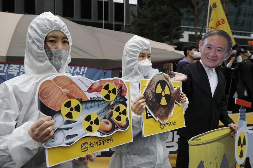 Activistas ambientales con una máscara del primer ministro japonés Yoshihide Suga