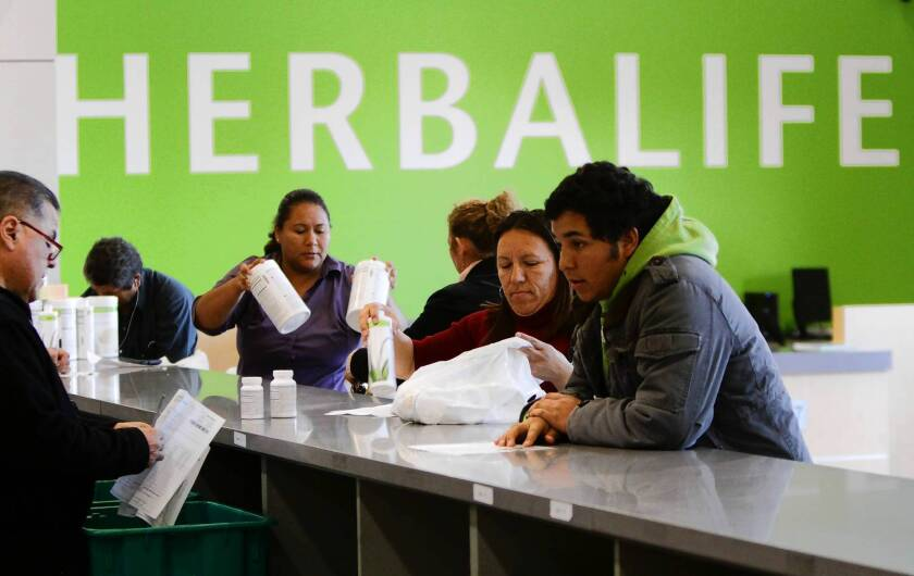 Herbalife's third-quarter sales grew 19.3% to $1.2 billion. Above, distributors line up at the nutritional products maker's distribution center in Carson.