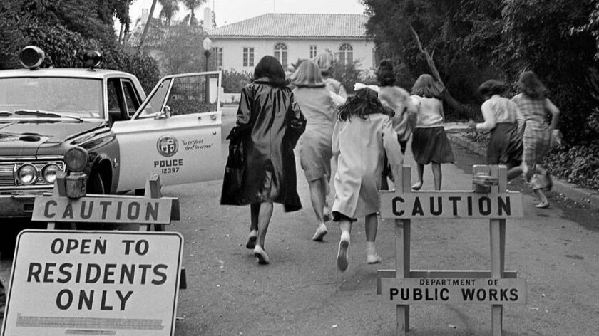 Aug. 25, 1964: Beatle fans run pass barricades and rush policemen in effort to reach the Bel-Air hom