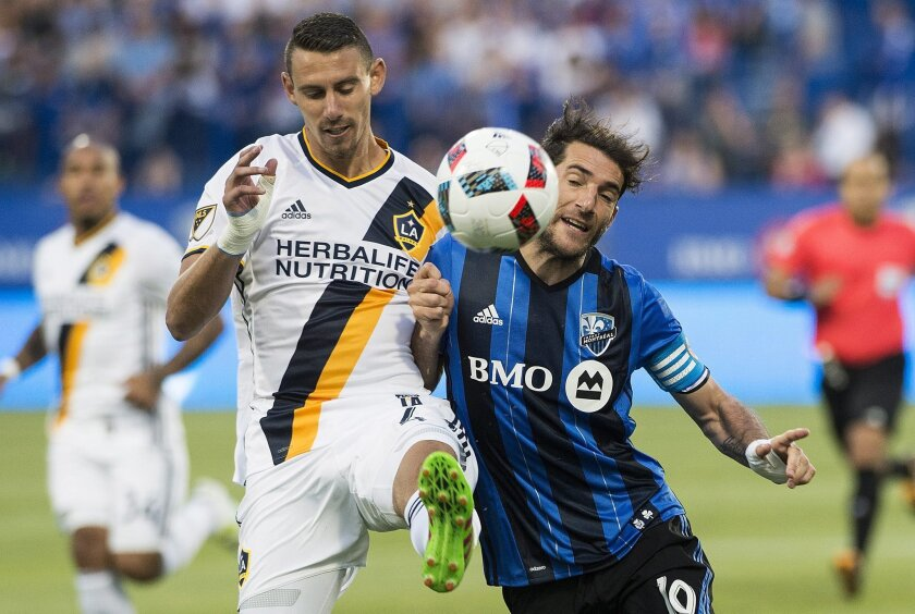 Montreal Impact's Ignacio Piatti, right, challanges Los Angeles Galaxy's Daniel Steres during first-half MLS soccer game action in Montreal, Saturday, May 28, 2016. (Graham Hughes/The Canadian Press via AP) MANDATORY CREDIT