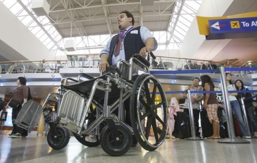Nicholas Gonzales, a wheelchair attendant, waits for a passenger at LAX. The U.S. Transportation Department filed fewer civil penalties against airlines for violating aviation laws in the last three years, according to an analysis by The Times.