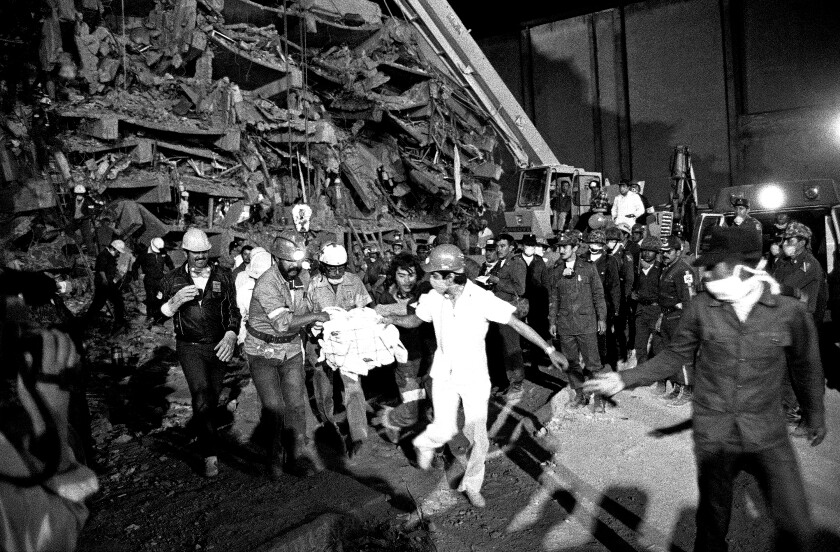 Emergency workers carry hospital patient Rubalcada Pena after rescuing him from the rubble of Mexico City's Juarez Hospital