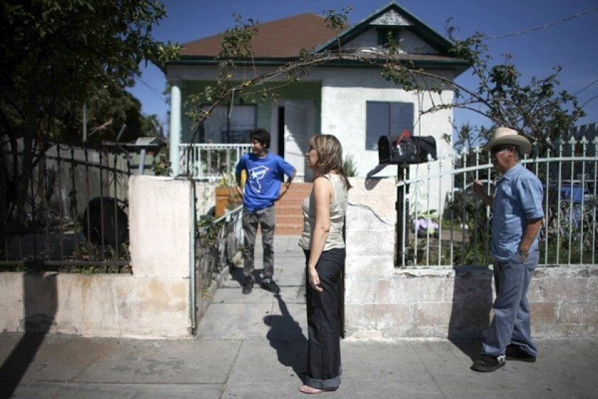 Adela Barajas, center, outside the family home on Long Beach Avenue. Her brother was shot and stabbed near here, and her sister-in-law was gunned down.