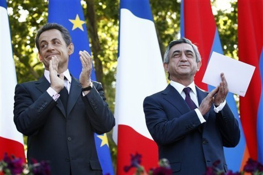 French President Nicolas Sarkozy, left, and Armenian President Serge Sarkisian applaud at the French Square, in Yerevan, Armenia, Friday, Oct. 7, 2011. Sarkozy has urged Turkey to recognize the 1915 massacre of Armenians by Ottoman Turks as genocide. Sarkozy said Friday during a news conference in the Armenian capital that Turkey's refusal to do so would force France to change its law and make such denial a criminal offense. (AP Photo/PanARMENIAN, Tigran Mehrabyan)
