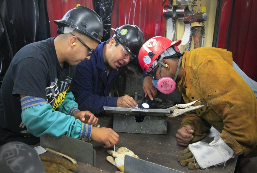 Instructors Carlos Hurtado, left, and Victor Clayton, center, make a visual inspection of a weld test plate with Deshaun Dillard, a student in the new-hire trade program at General Dynamics-NASSCO on July 10. / photo by Howard Lipin * U-T San Diego