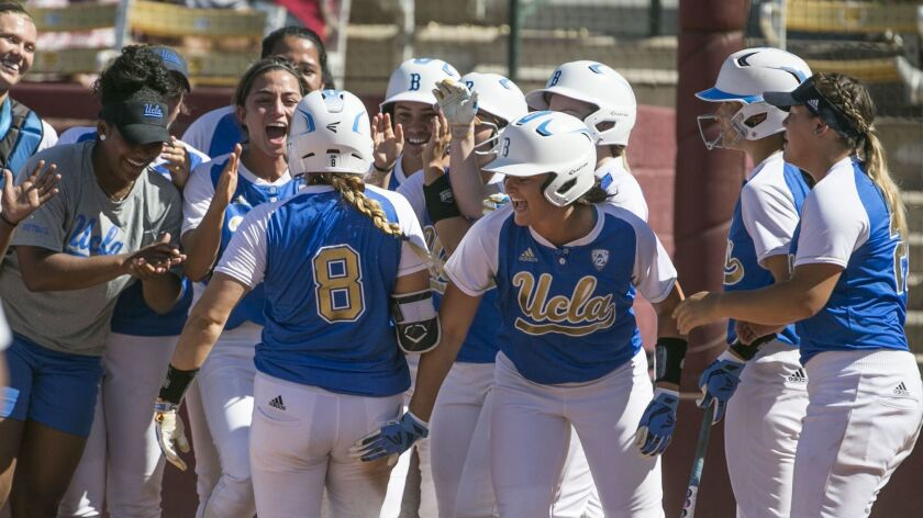 UCLA's Kylee Perez (8) is greeted at home by teammates after hitting a grand slam against Arizona State on May 13.