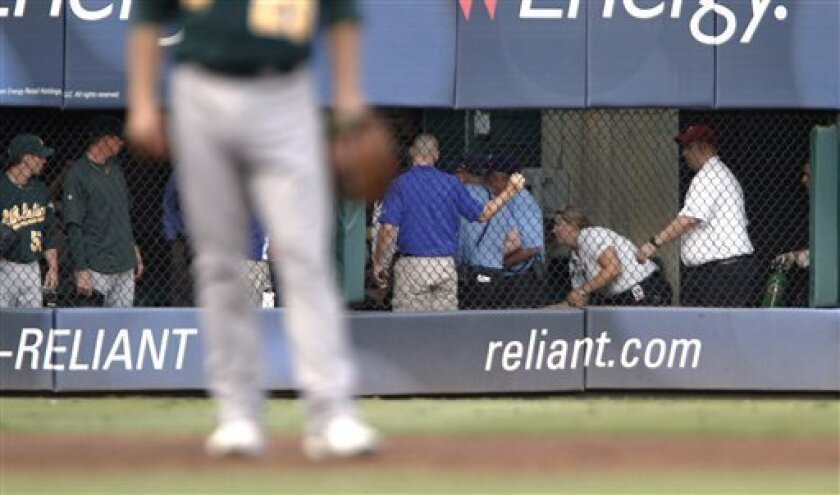 Emergency workers tend to a man who fell out of the stands while trying to catch a baseball tossed his way during a game between the Texas Rangers and the Oakland Athletics on Thursday, July 7, 2011, in Arlington, Texas. The Rangers said the fan died after the fall of about 20 feet. (AP Photo/Jeffery Washington)