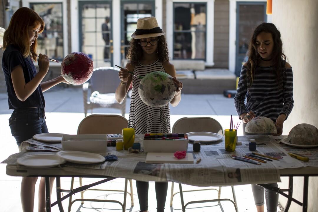 Kat Bristow, left, Carmen Furbush and Penelope Roth work on papier-mache masks in art class inside the Roths' garage.