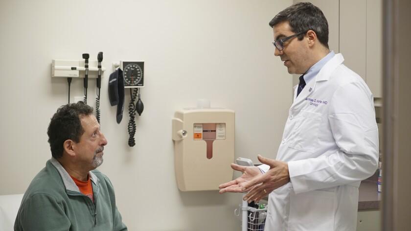 El paciente Daniel Lobello, a la izquierda, habla con el doctor Matthias Hofer, urólogo