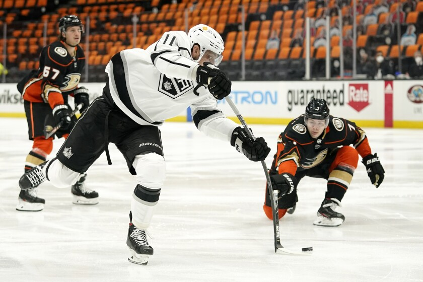 Kings center Anze Kopitar shoots as Ducks defenseman Ben Hutton defends.