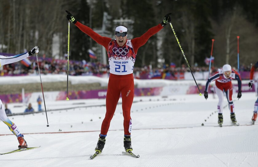 Switzerland's Dario Cologna crosses the finish line to win the men's cross-country 30k skiathlon at the 2014 Winter Olympics, Sunday, Feb. 9, 2014, in Krasnaya Polyana, Russia. (AP Photo/Gregorio Borgia)