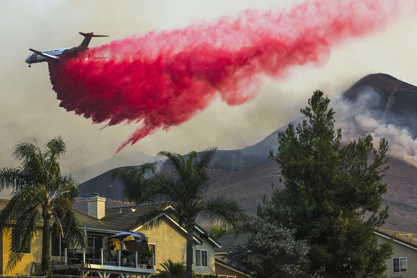 An air tanker drops fire retardant behind homes Tuesday in Chino Hills.
