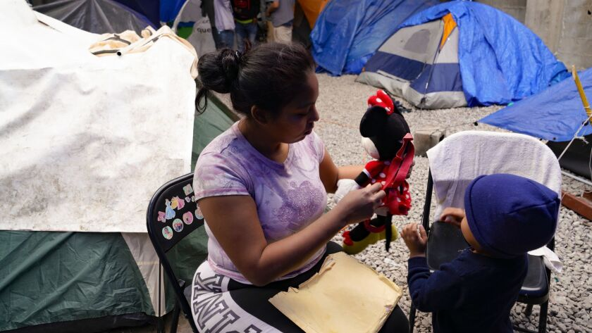 At a Tijuana migrant shelter, Karen tends to her youngest child. Karen, who is from Honduras, has requested asylum for herself and her three children in the U.S., and waits in Tijuana for her court date in the U.S.