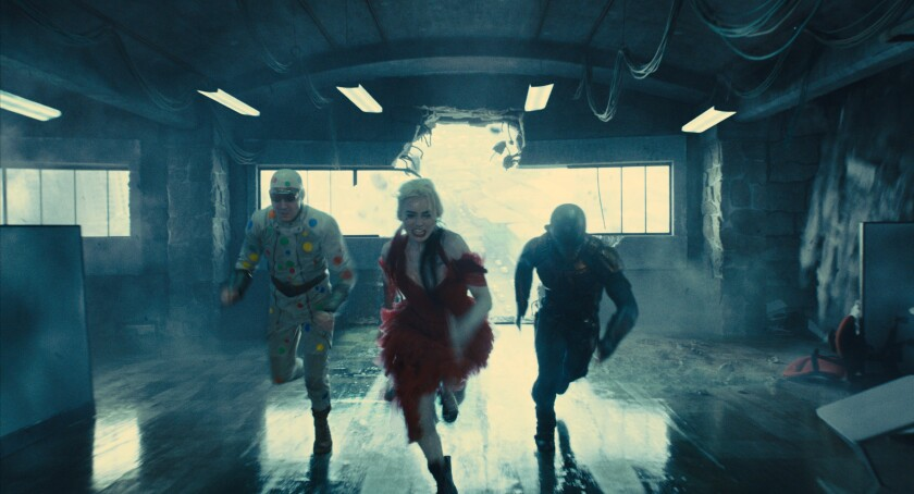 A man in a polka dot suit, a woman in a dress and a man with a helmet running