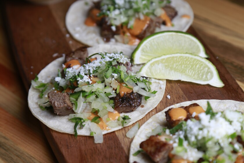 Barbacoa tacos made with chile braised brisket, cilantro, onion queso cotija, salsa adobo and a soft corn tortilla.