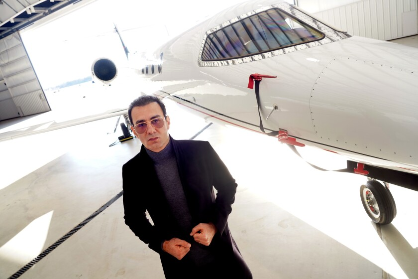 Richard Zaher stands next to a private jet.