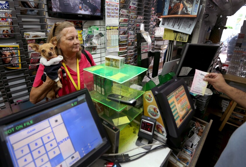 Marie Steele holds her dog, Little Bit, as she purchases a Mega Millions lottery ticket at a newsstand in Hollywood, Fla.