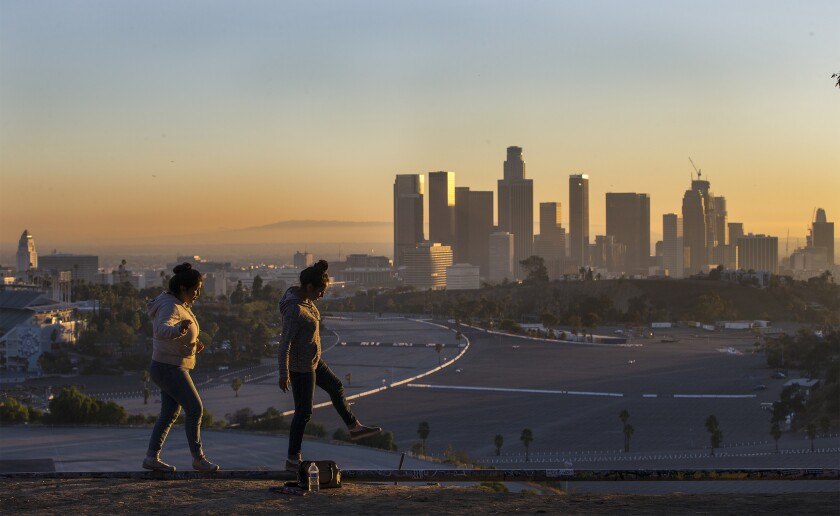 With the L.A. skyline in the background, Stacey Martinez and Jessica Arellano balance on an old irrigation pipe on a dry slope at Angels Point in Elysian Park. LA's temperature is expected to rise 5 degrees by midcentury, and public health officials are worried about what that'll mean for Angelenos.