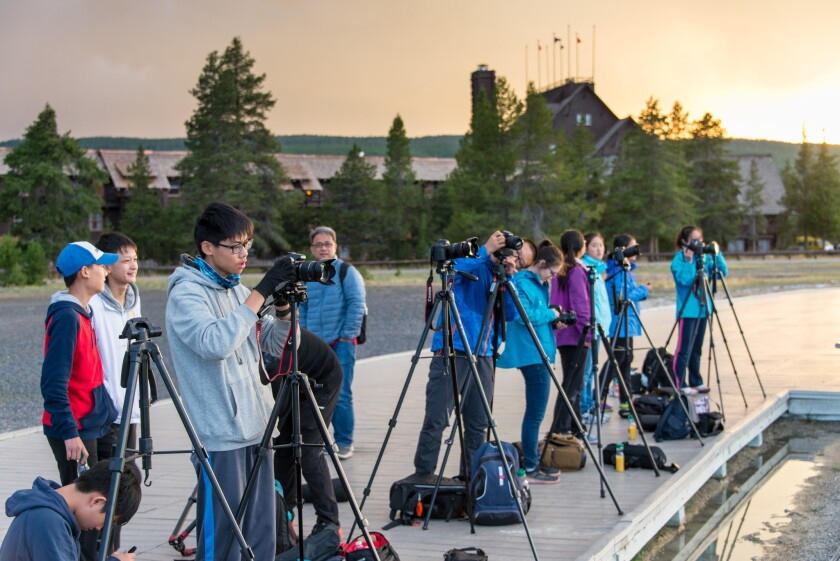 Photographers gather for an evening shot of the Old Faithful Geyser's eruption, in front of the hi