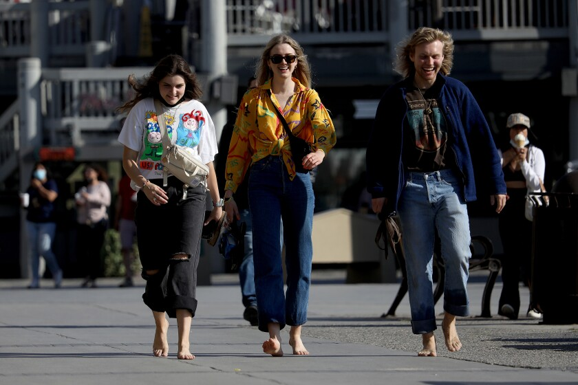Three women walk without masks along the boardwalk in Redondo Beach on Tuesday
