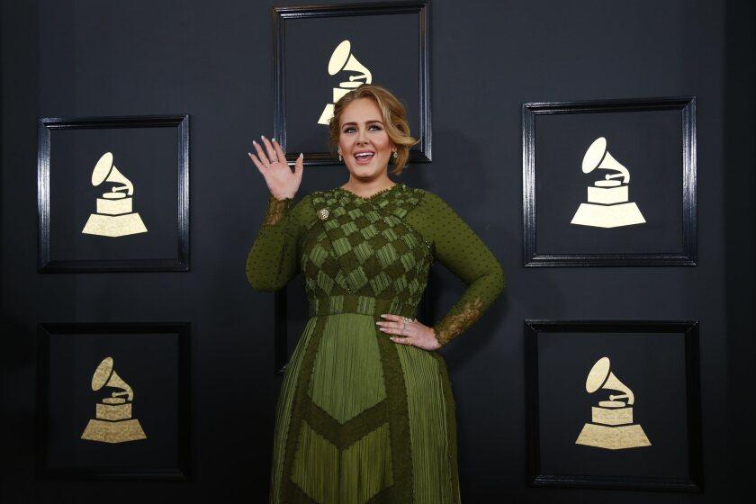 A woman waving in a green dress