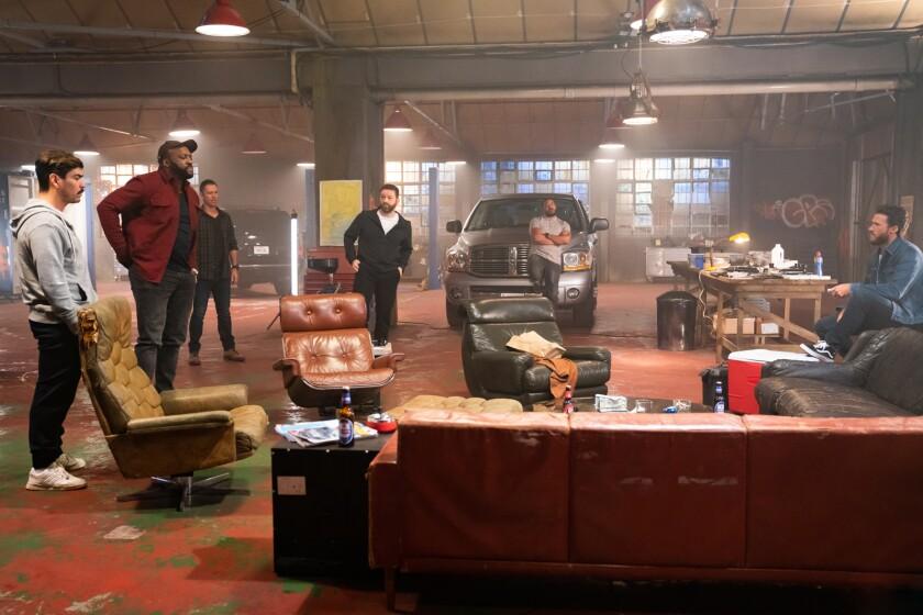Five men in a warehouse.