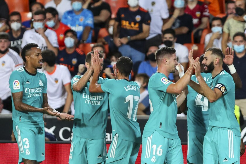 Real Madrid's Vinicius Junior celebrates with teammates after scoring his side's first goal during a Spanish La Liga soccer match between Valencia and Real Madrid at the Mestalla stadium in Valencia, Spain, Sunday, Sept. 19, 2021. (AP Photo/Alberto Saiz)