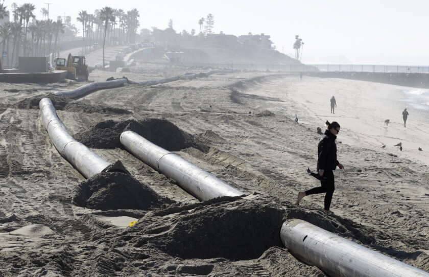 A beachgoer crosses dredging pipe on the beach in Carlsbad just south of Tamarack Beach on Friday.