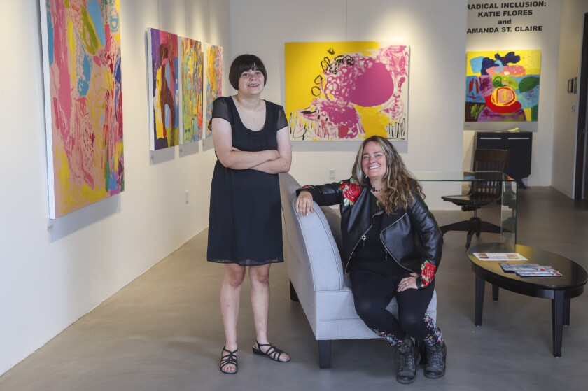 Painters Amanda Saint Claire (right) and Katie Flores pose for photos with their collaborations at an art gallery