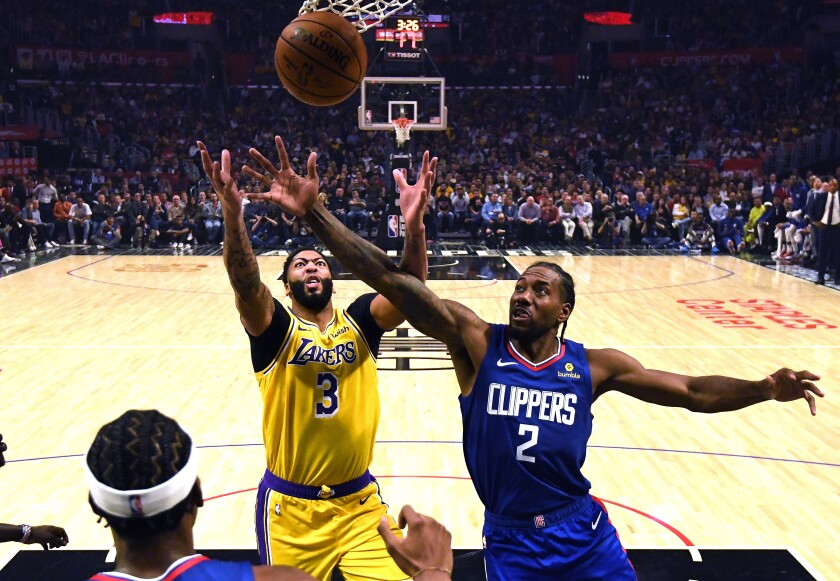 Lakers forward Anthony Davis, left, battling Clippers forward Kawhi Leonard for a rebound on Oct. 22, helped make their new teams instant title contenders.