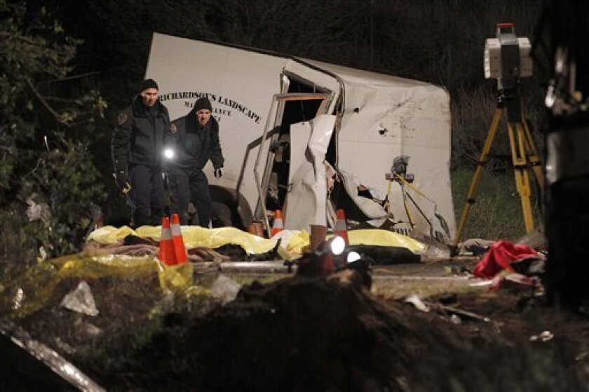 Investigators examine body bags of victims near the scene where at least eight people were killed and 38 people were injured after a tour bus carrying a group from Tijuana, Mexico crashed with two other vehicles near Yucaipa, Calif., Sunday, Feb. 3, 2013. (AP Photo/Nick Ut)