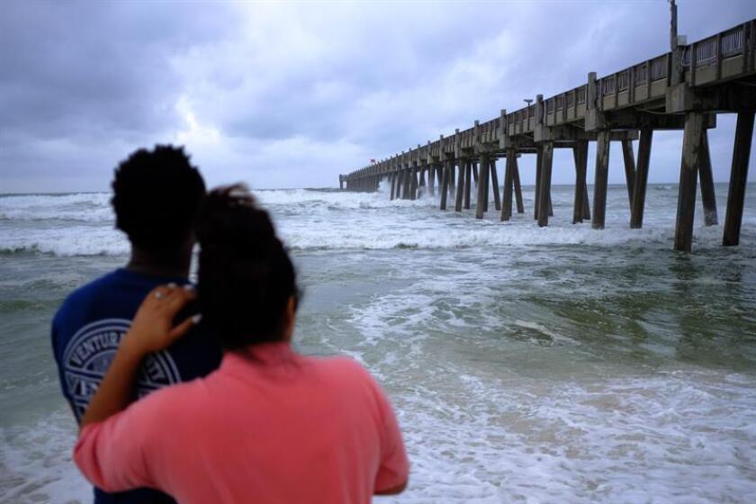 Una pareja observa el movimiento de las aguas en una playa en Pensacola ante el paso cercano del huracán Michael, en Florida, Estados Unidos, hoy, 9 de octubre de 2018. EFE