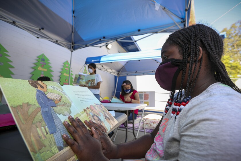 Nyairee Jenkins, right, reads a book in an outdoor class under a canopy at Freedom Schools.