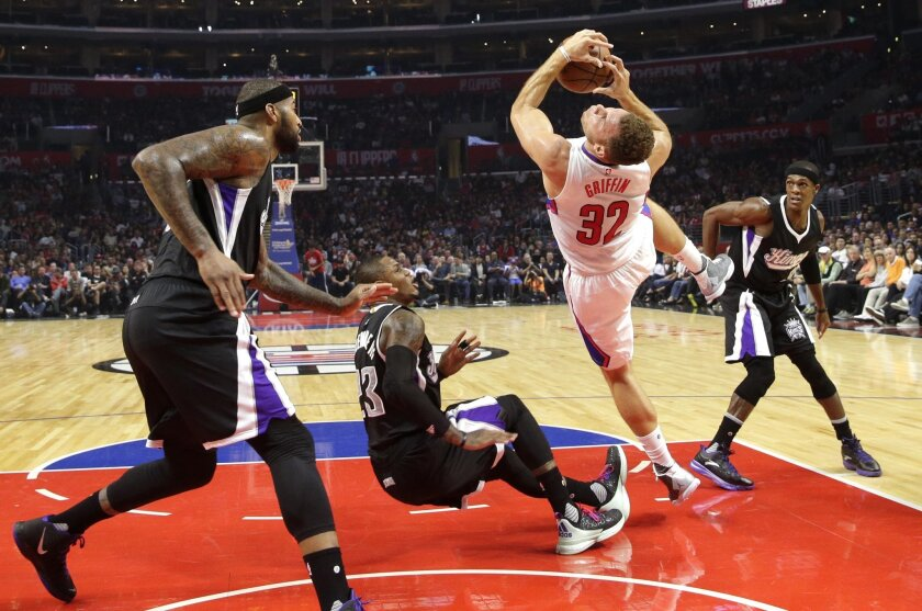 Los Angeles Clippers' Blake Griffin, center right, is fouled by Sacramento Kings' Ben McLemore, center left, as Kings' DeMarcus Cousins, left, and Rajon Rondo, right, watch during the first half of an NBA basketball game, Saturday, Oct. 31, 2015, in Los Angeles. (AP Photo/Jae C. Hong)